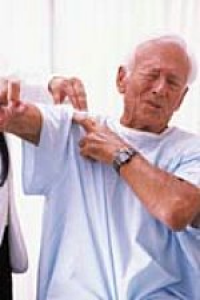 Man whincing as he lifts his arm
