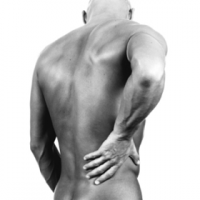 Man standing holding his back